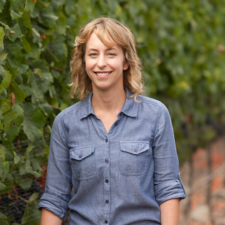 Lorna Kruetz, Winemaker, Fog Theory Wines standing with large grape vines in background.