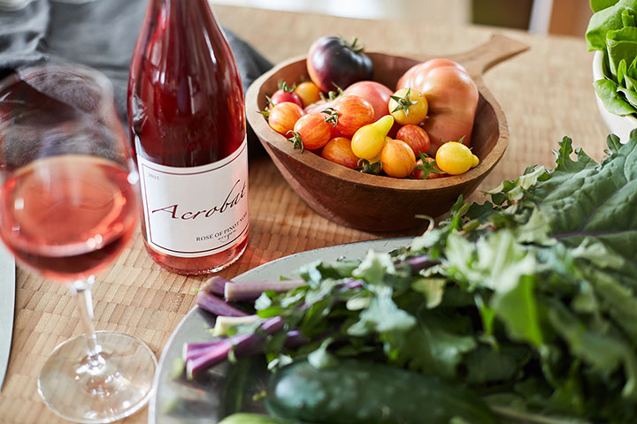 Glass and Bottle of Acrobat Rose on Table With Heitrloom Tomatoes