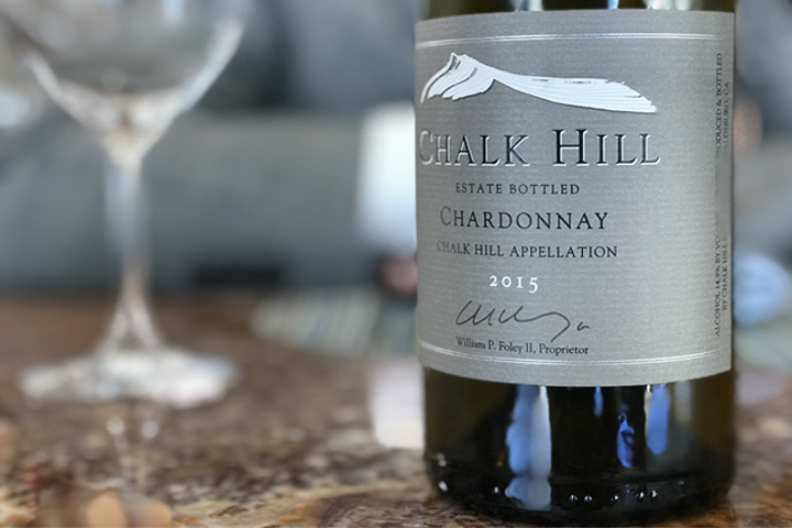 Image of the 15 Chardonnay bottle with a glass of Chardonnay in the background