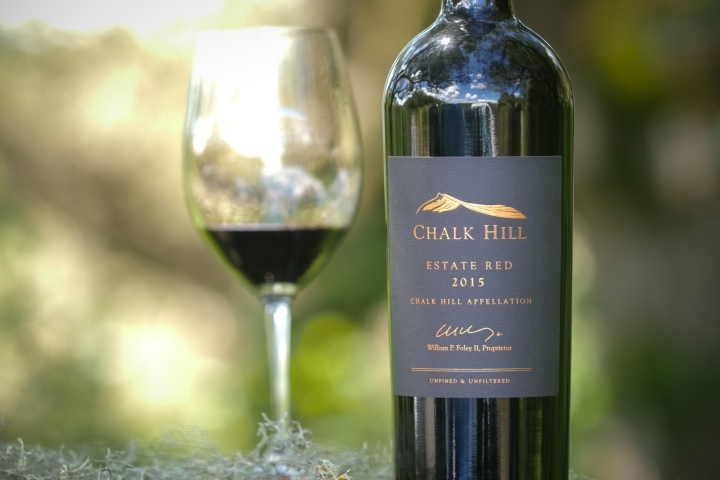 Portrait picture of Chalk hill Estate red wine bottle with full wine glass in the background