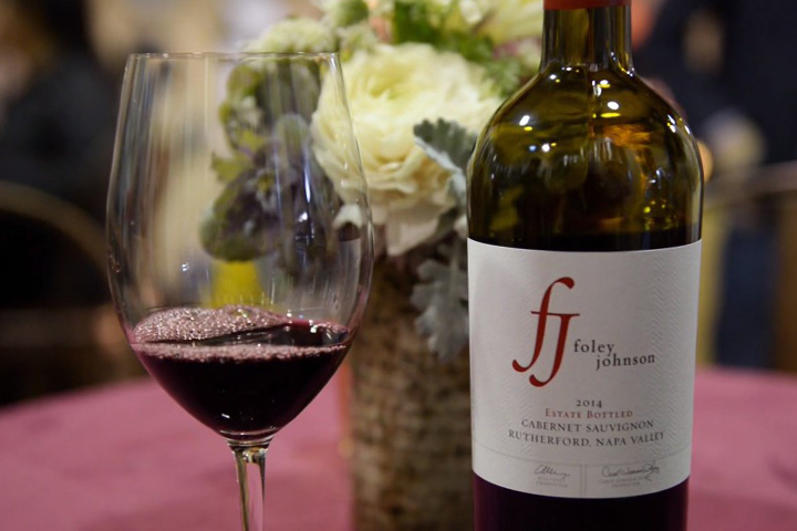 Bottle of Foley Johnson Cabernet sitting next to a glass of the Cab, with flowers in the background