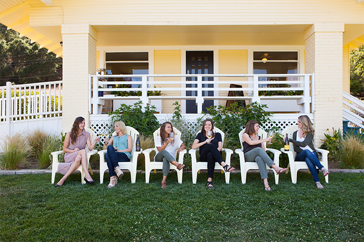 Ladies sipping wines while sitting on Adirondack chairs