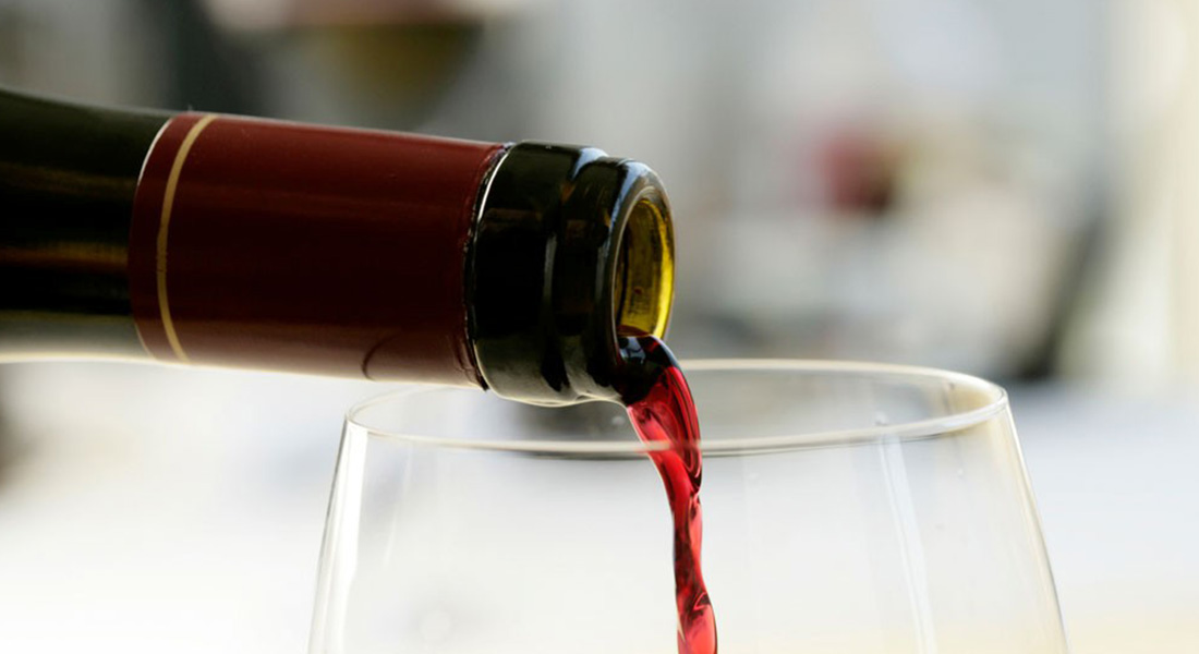Red wine pouring from a bottle to a glass