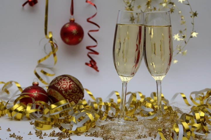 two glasses of champagne with tinsel and Christmas ornaments surrounding them