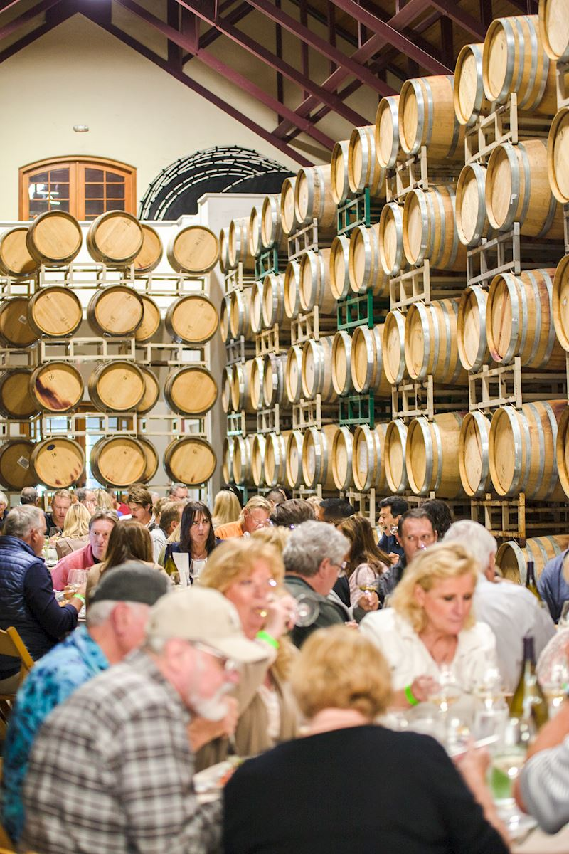 Event attendees enjoying themselves amongst Foley Estate wine barrels.