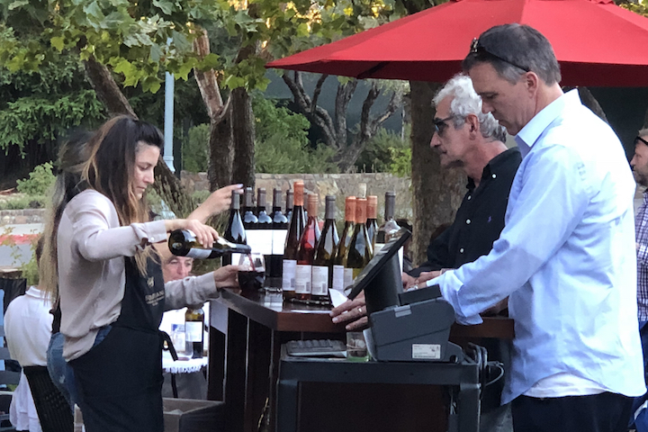 Outside tasting bar at a winery with guests anxiously waiting for their next pour from the tasting room associate