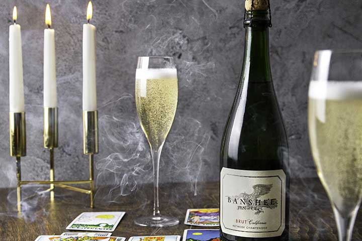 Banshee sparkling wine on a table with candles and champagne flutes