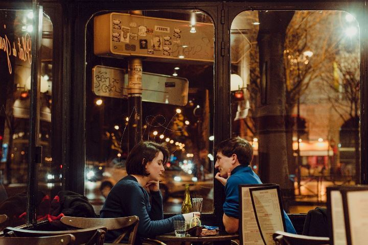 Couple enjoying a bottle of wine in a restaurant alone at night time