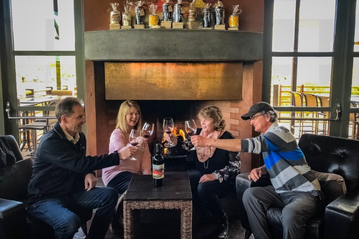 Group of four adults cheer-zing wine glasses together during a tasting