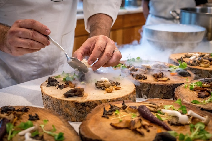 A chef preparing a gourmet meal on slabs of circular wood plates