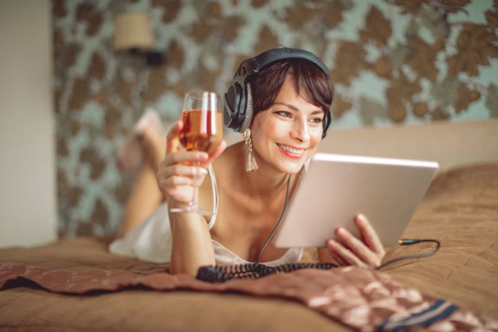Woman Listening to Podcast and Drinking Wine