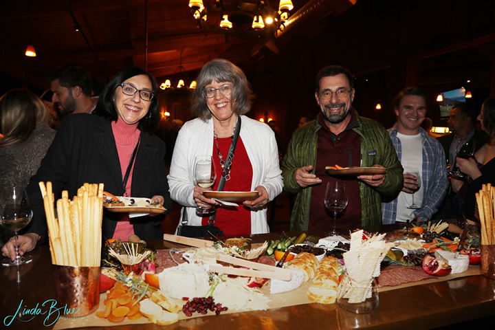 4 Guests Smiling at the Charcuterie Table