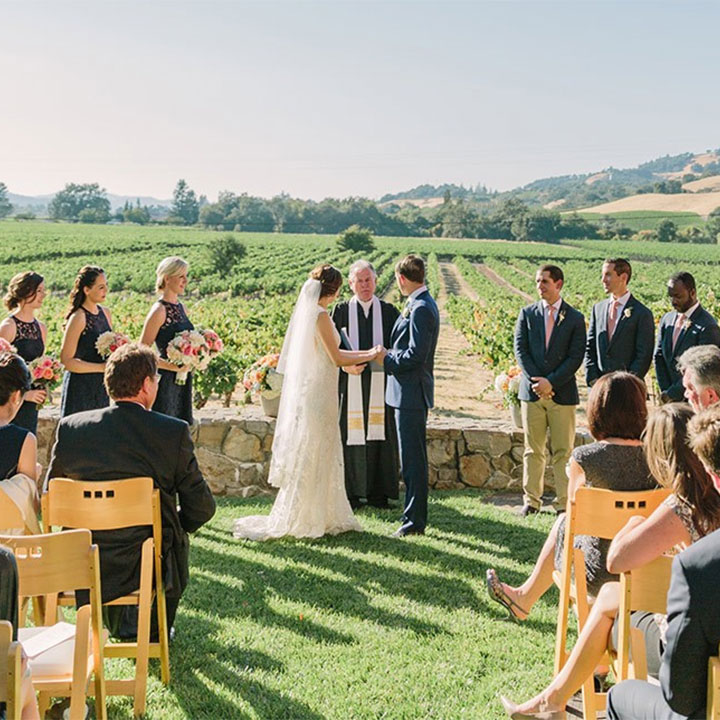 Wedding ceremony with vineyard in the background.