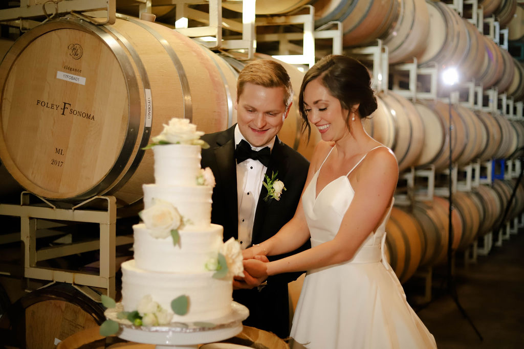 Bride and Groom Cutting Wedding Cake in Barrel Room