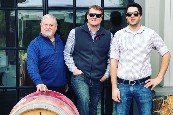 Three guys standing behind a wine barrel.
