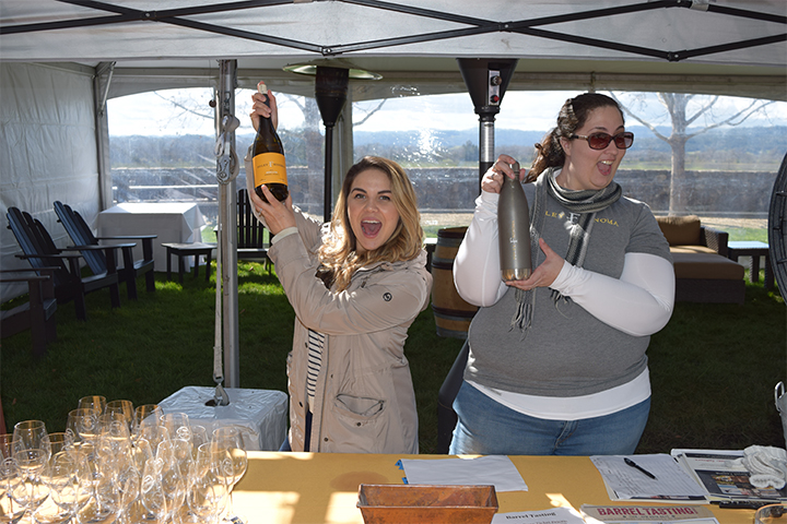 Two Girls holding up Foley Sonoma Wine bottles at a check in booth for Barrel Tasting.