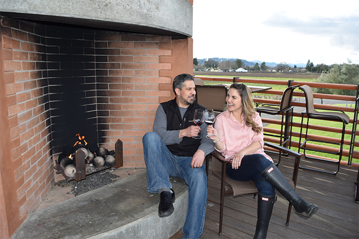 A man and woman sitting by the outdoor fireplace at Foley Sonoma with glasses of wine.