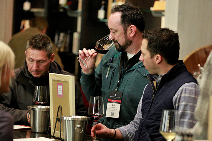 Men tasting wine at the Foley Johnson PNV Party.