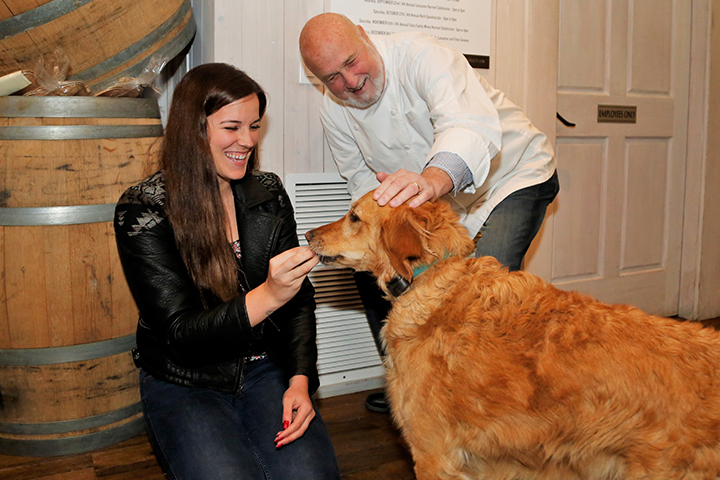 Executive Chef Larry Forgione and a woman petting Winemaker Patrick Foley