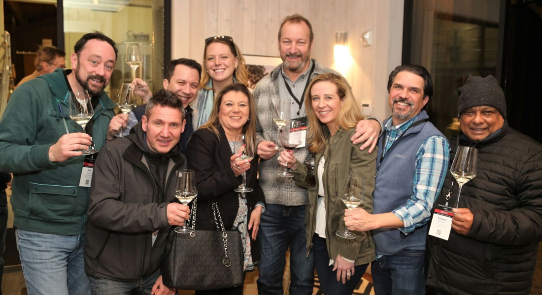 A group of wine tasters posing together at the PNV Kickoff Party at Foley Johnson.