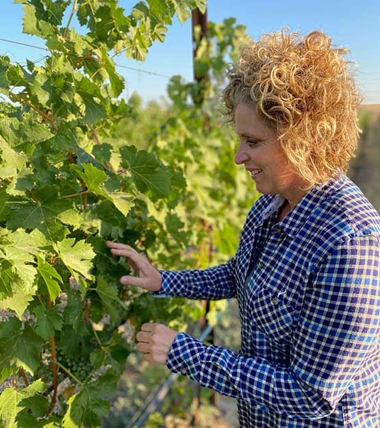 Holly Turner Inspecting Grapes in the Vineyard