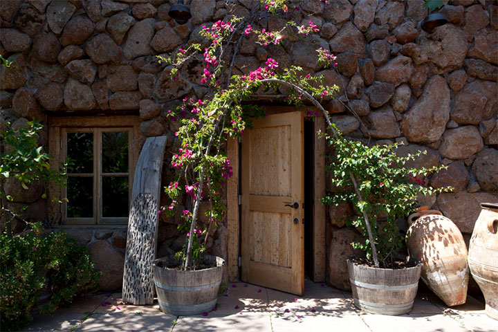 Wooden Door With Flower Arch in a Stone Wall