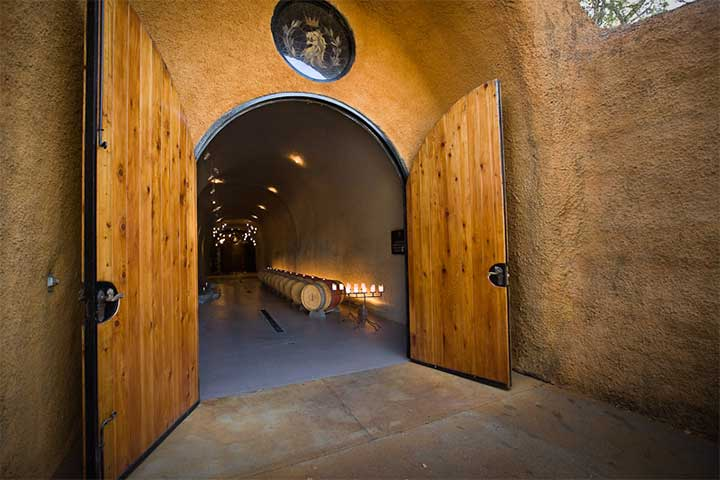 Entrance to the Wine Cave With a Row of Barrels Showing