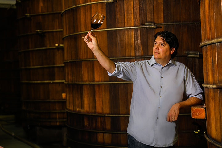 Winemaker, Walter Jorge with Wine Glass in Hand Standing in Front of Wine Barrels