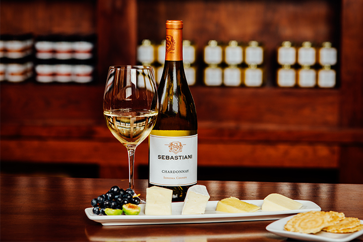 A glass and bottle of Sebastiani Chardonnay, next to a cheese and fruit plate, with a side of crackers
