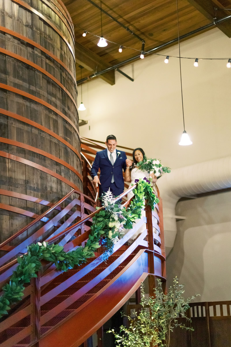 Married Couple Walk Down Curved Stairway Encircling Giant Historic Cask