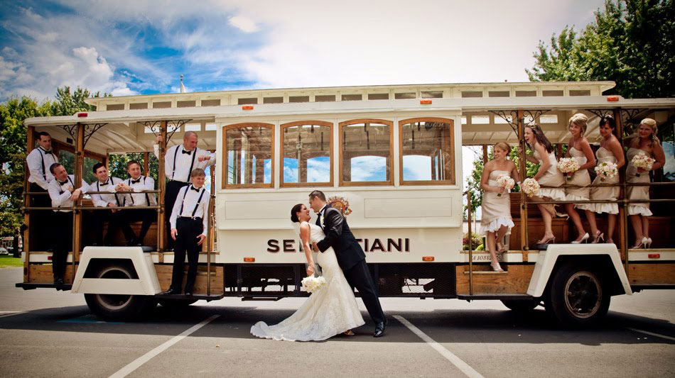 Bride and Groom in Dip Pose in front of Sebastiani Trolley with the Bridesmaids and Groomsmen on the Trolley