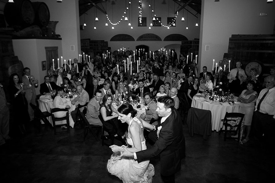 Black and White Photo of Bride and Groom Dancing with Wedding Guest Seated at Tables Watching