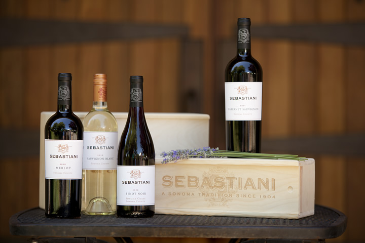 Bottles of Sebastiani Red and White Wines Setting on a Table with Wine Barrels in Background