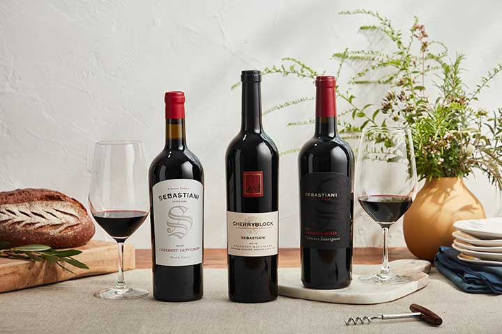 Bottles of three Sebastiani Cabernet Sauvignon paired with food on a table