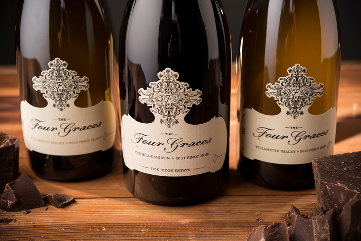 Three Bottles of Four Graces Wines Arranged on a Table