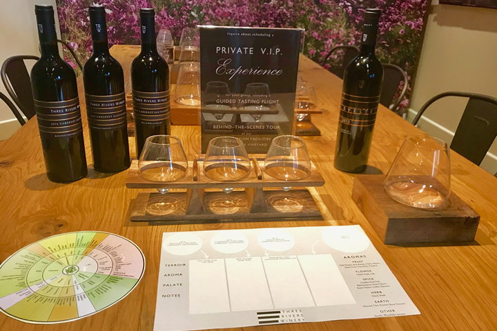 A Flight of Wine Glass, Tasting Notes and Wine Bottles on Table