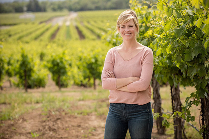Chalk Hill Winemaker, Courtney Foley, standing in a springtime vineyard at Foley Sonoma.