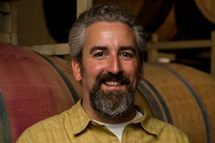 David Drake, Winemaker at Lancaster Estate, standing in front of barrels in the Lancaster Estate Cave.