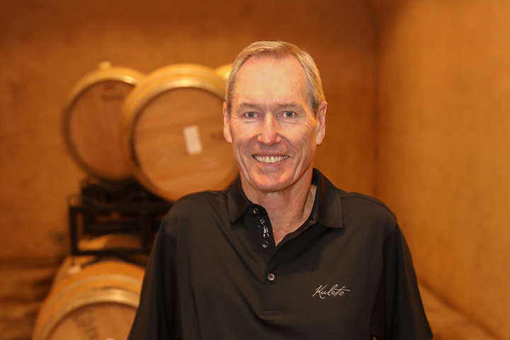 John Clews, Kuleto Winemaker, in a wine cave standing in front of wine barrels.