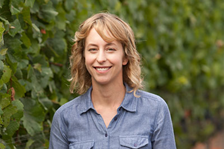 Lorna Kreutz, Lincourt Director of Winemaking, standing in a lush green Lincourt vineyard.